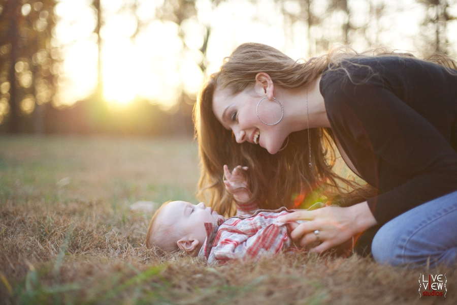 mother smiling at baby in sunlight, baby photography nc