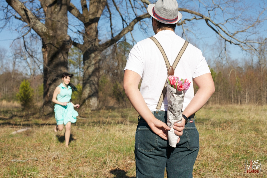 romantic retro couple's photography, man holding flowers wrapped in newspaper for his love