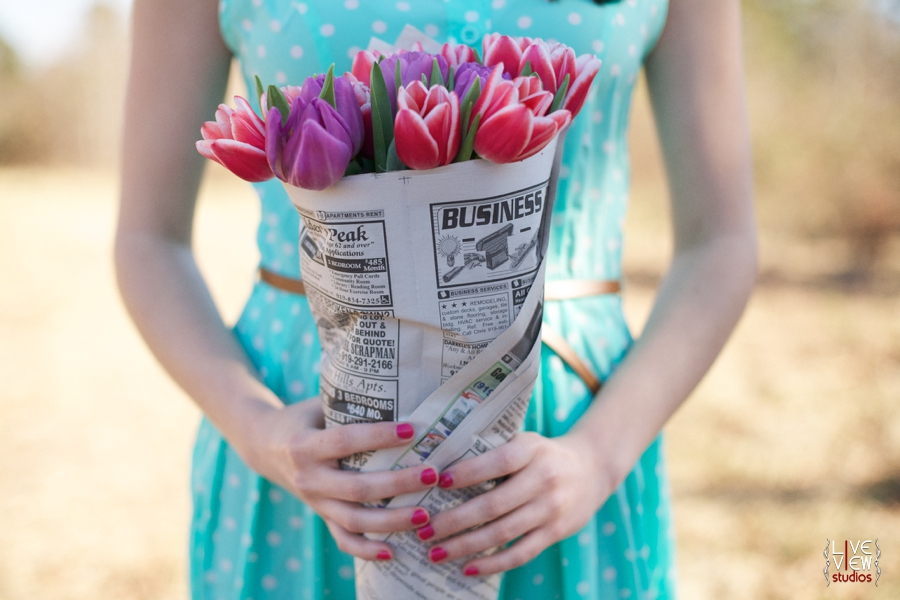 woman holding pink and purple tulips wrapped in newspaper, romantic valentine's day couple's photography