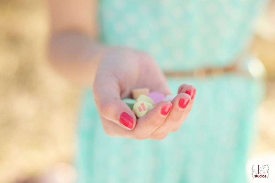 woman with pretty pink nails holding colorful sweetheart candies