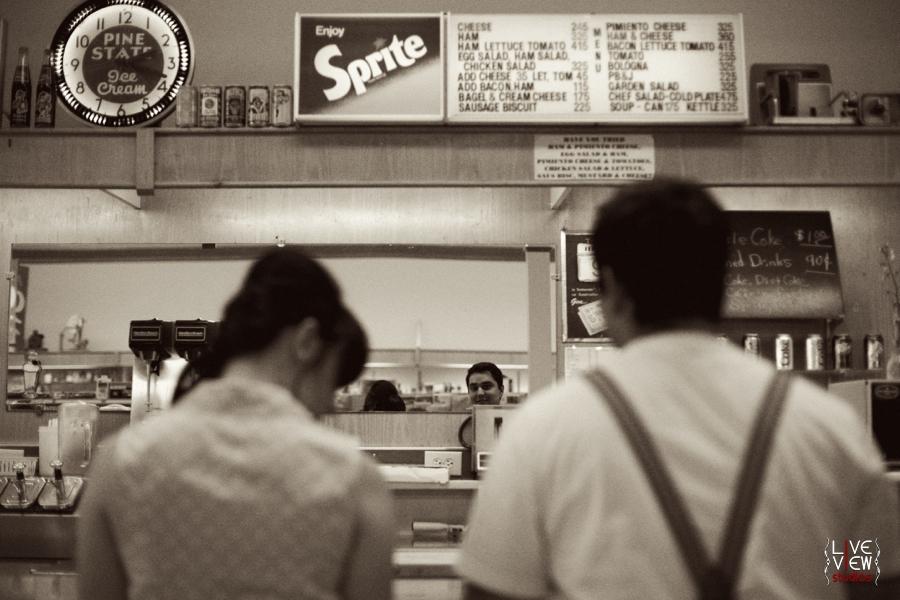 a young couple waiting at elliotts pharmacy, retro engagement photography