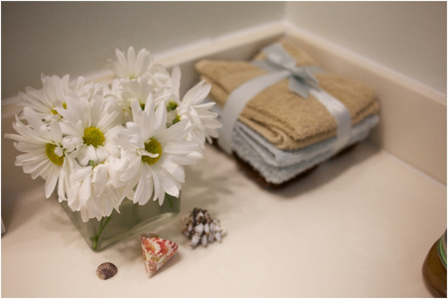 brown, blue, and tan terry washcloths tied with light blue ribbon, fresh flowers and sea shells as an affordable decoration to bathroom sink