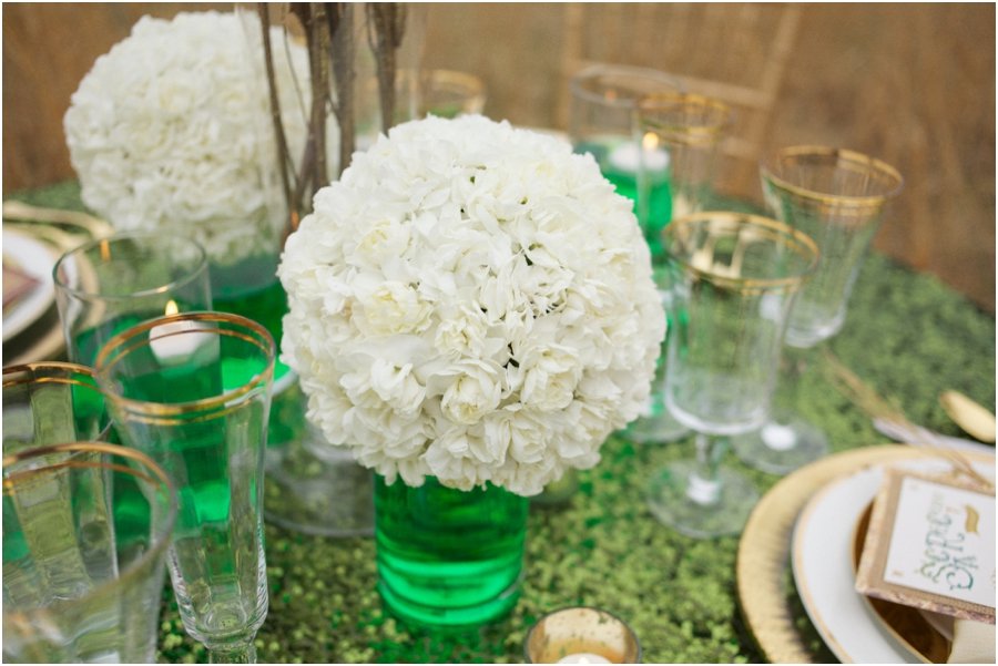 white floral pomanders in emerald tinted water on emerald sequin tablecloth, modern wedding reception ideas