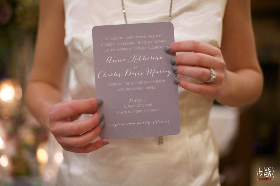 bride holding out wedding invitation, raleigh nc wedding photographers