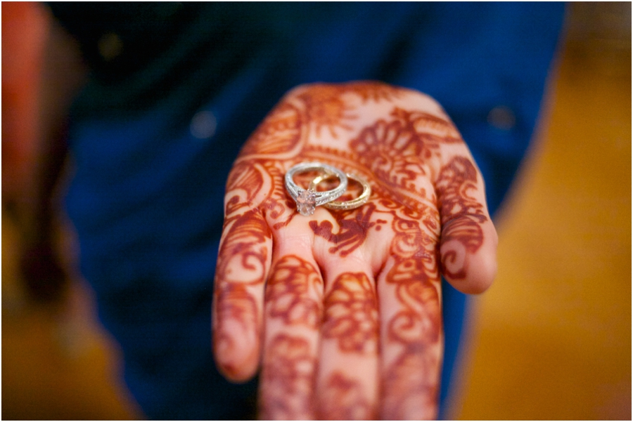 bride with henna hand tattoos holding out wedding rings