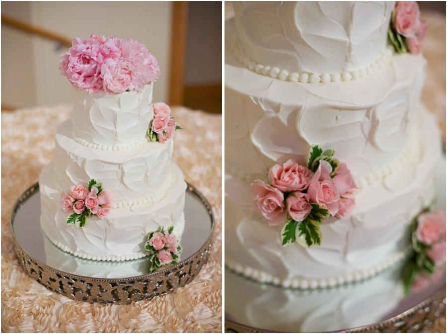 elegant strawberry buttercream wedding cake with fresh pink flowers from Maxie B's Bakery, pearl details on elegant wedding cake