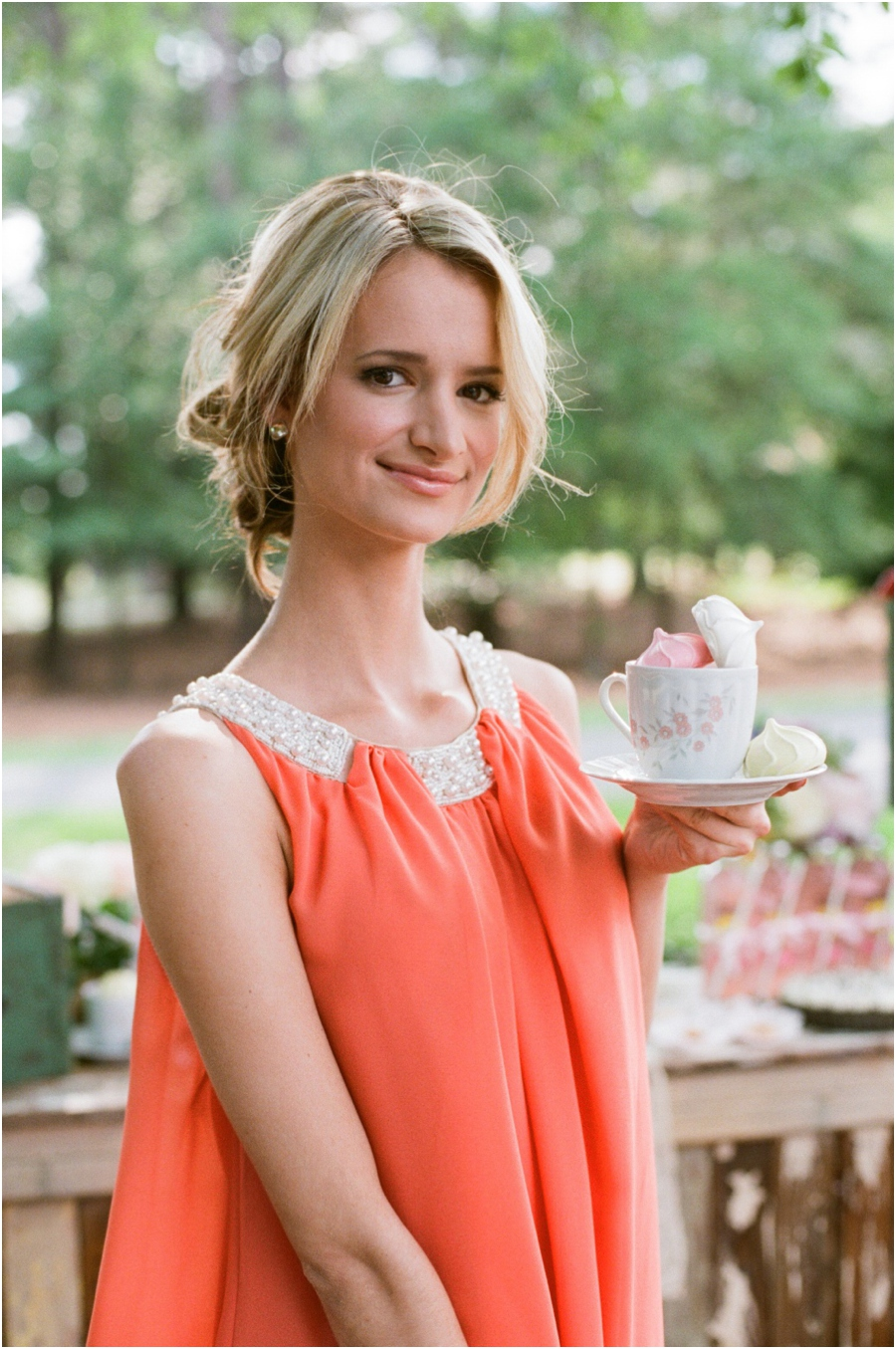 bridesmaid in coral dress holding vintage teacup with colorful meringues, southern wedding photographers