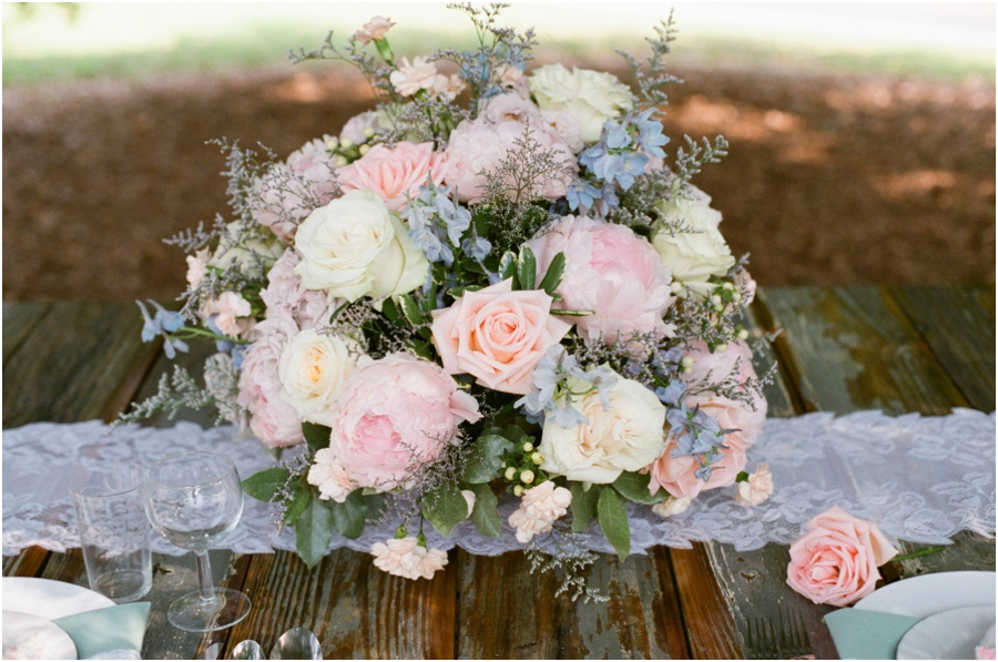 lush floral arrangement of peach and cream roses and pink peonies made by Embellished Blooms was set atop a vintage lace table runner for a centerpiece, rustic wedding photographers